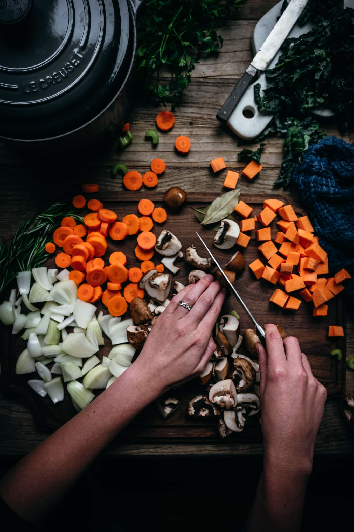 overhead view of person cutting mushrooms and other fall vegetables on a wood cutting board