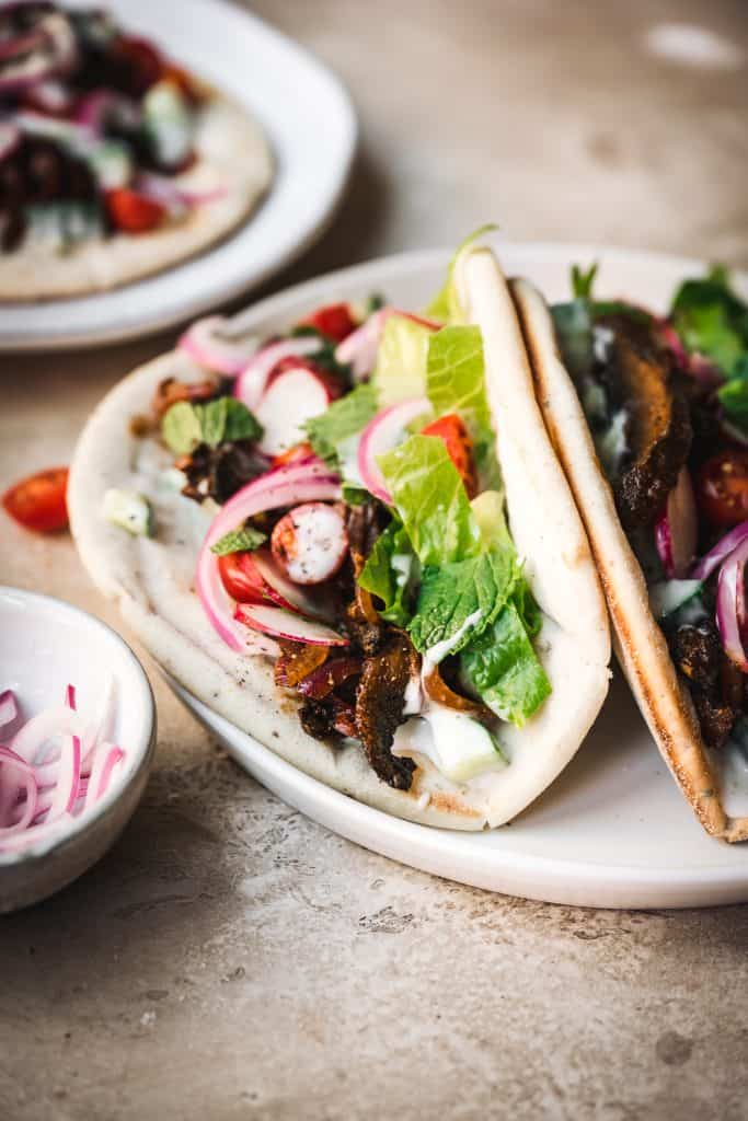 Close up side view of two mushroom shawarma in a pita bread on a white plate