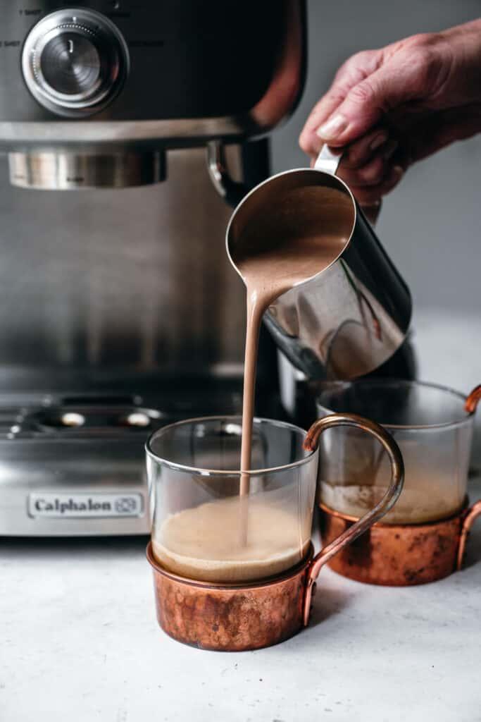 pouring homemade peppermint mocha creamer into espresso