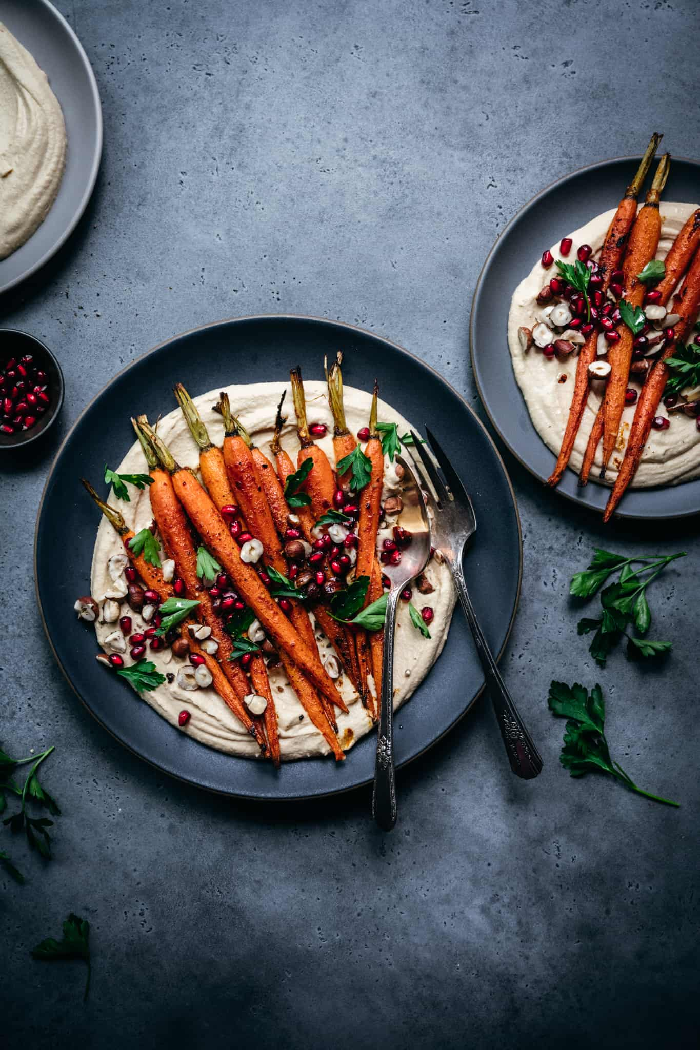 overhead view of harissa roasted carrots over a bed of hummus