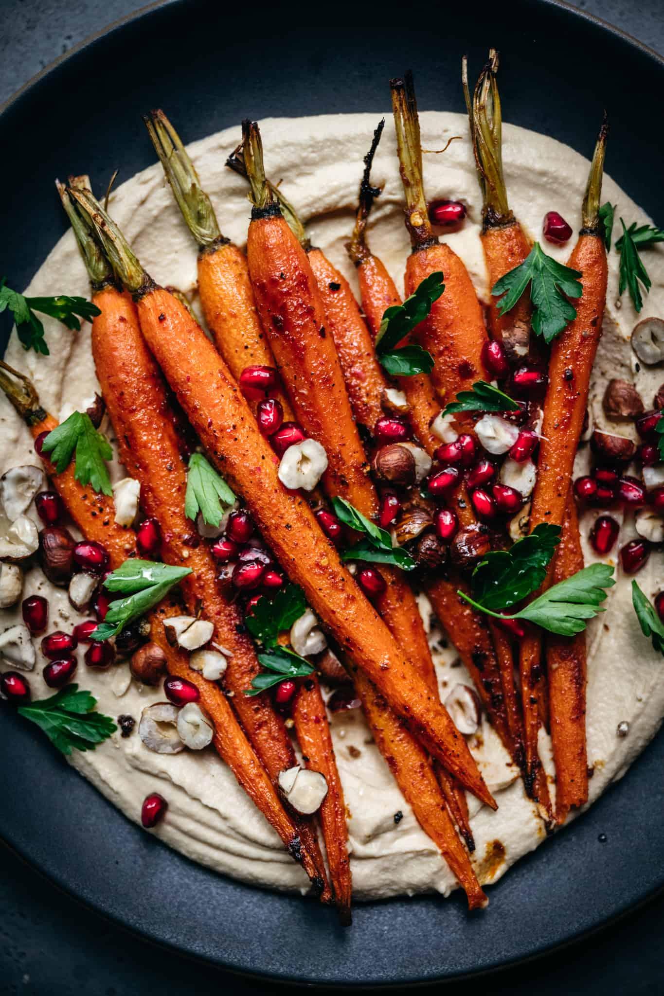 close up overhead of harissa roasted carrots on pumpkin hummus with pomegranate seeds