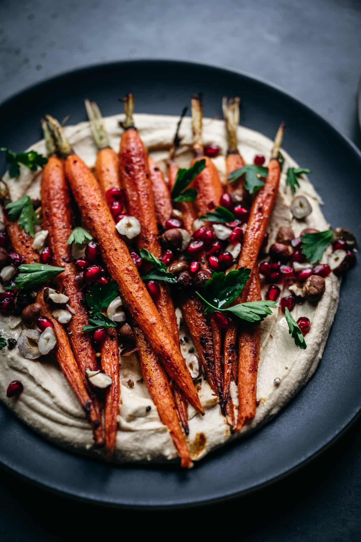 close up overhead of vegan harissa roasted carrots with pomegranate seeds and tahini dressing
