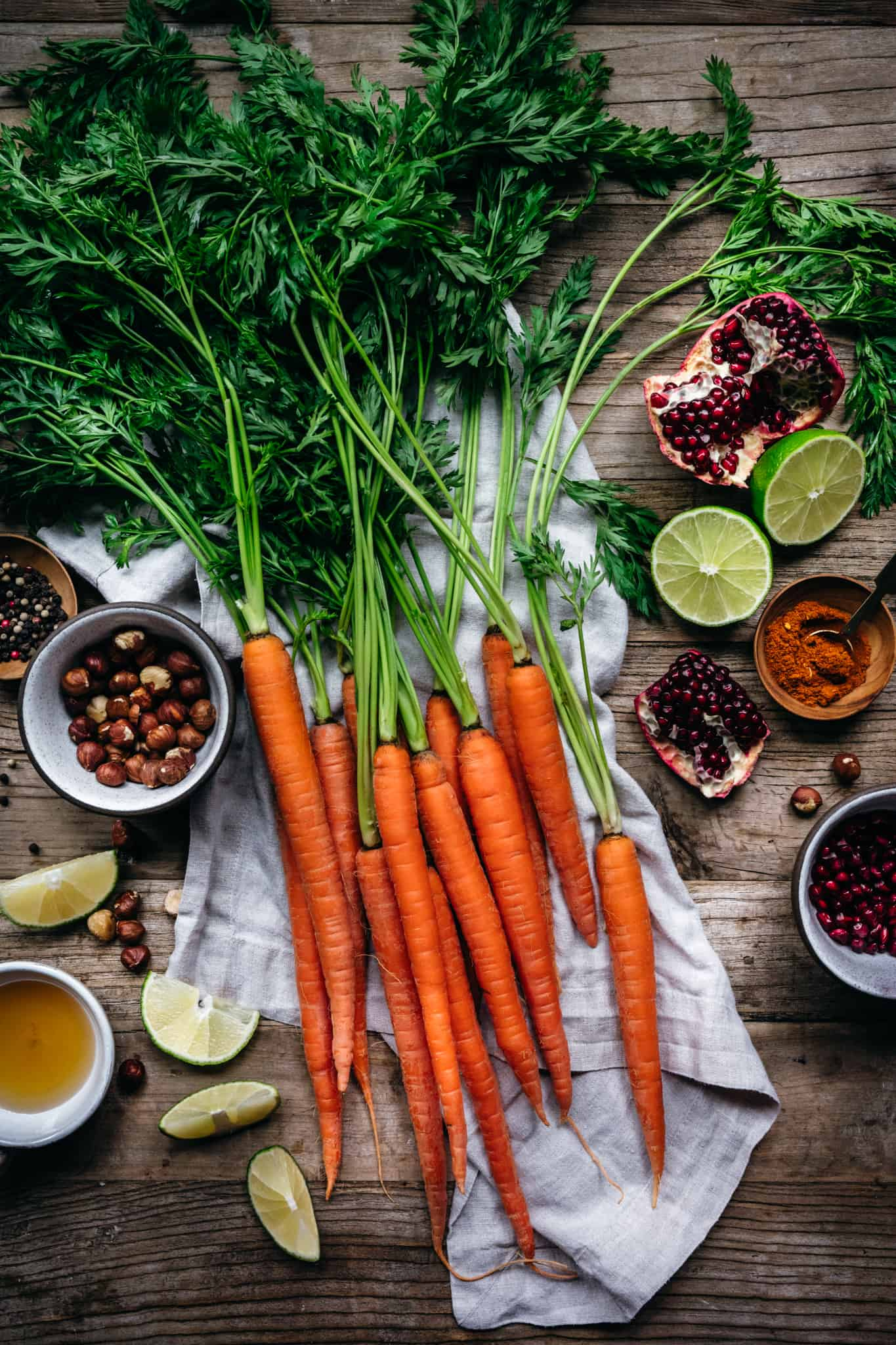 overhead of the raw ingredients for harissa roasted carrots on a wooden background