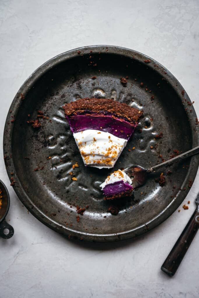 overhead view of slice of purple pie in antique pan