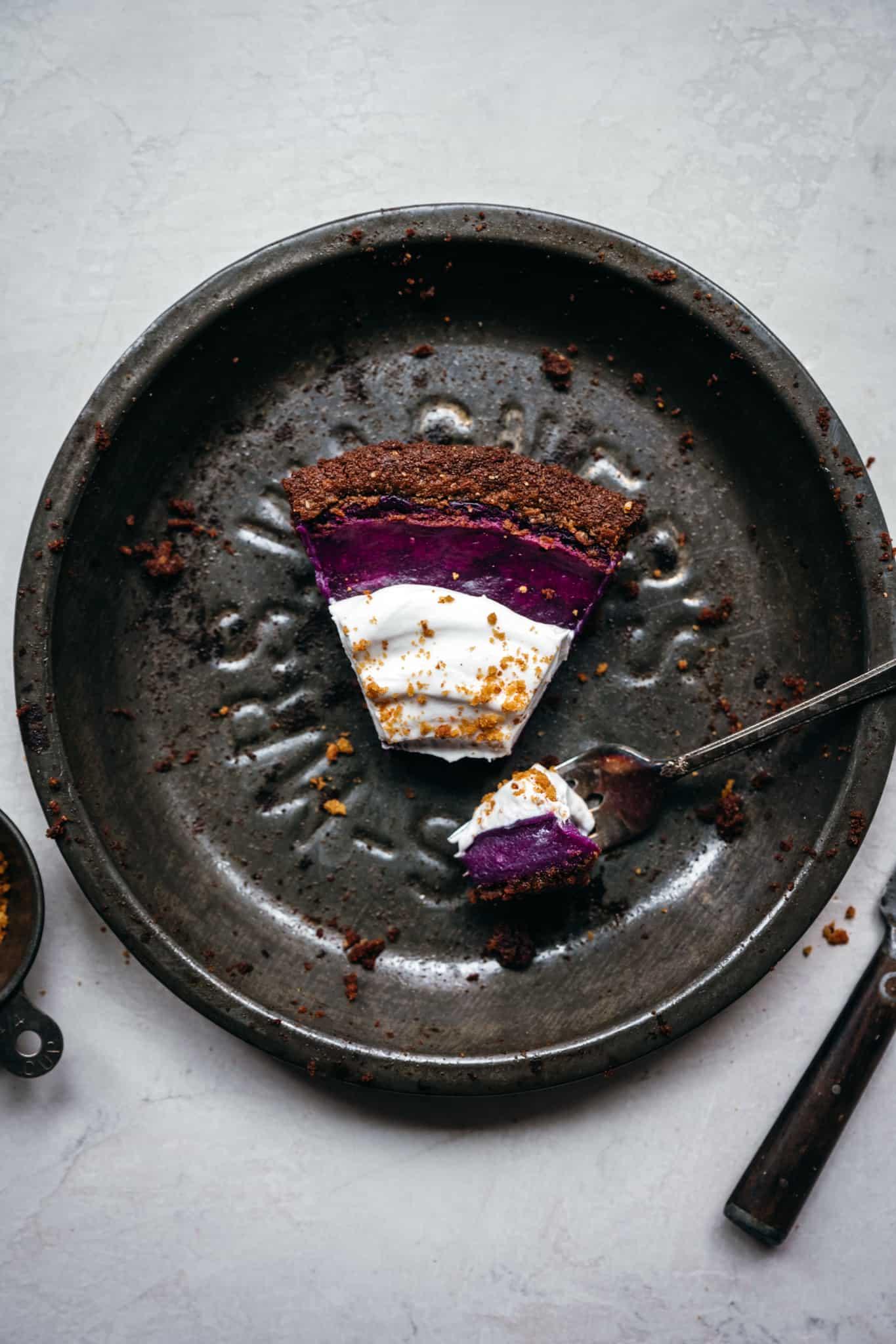 overhead view of slice of purple pie in antique pan