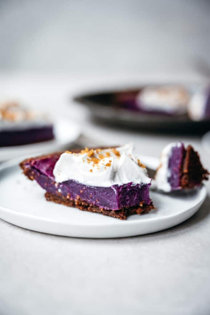 Side view of slice of vegan purple sweet potato pie on a white plate