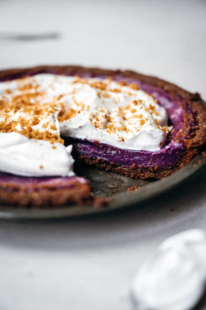 close up side view of purple sweet potato pie with whipped cream topping