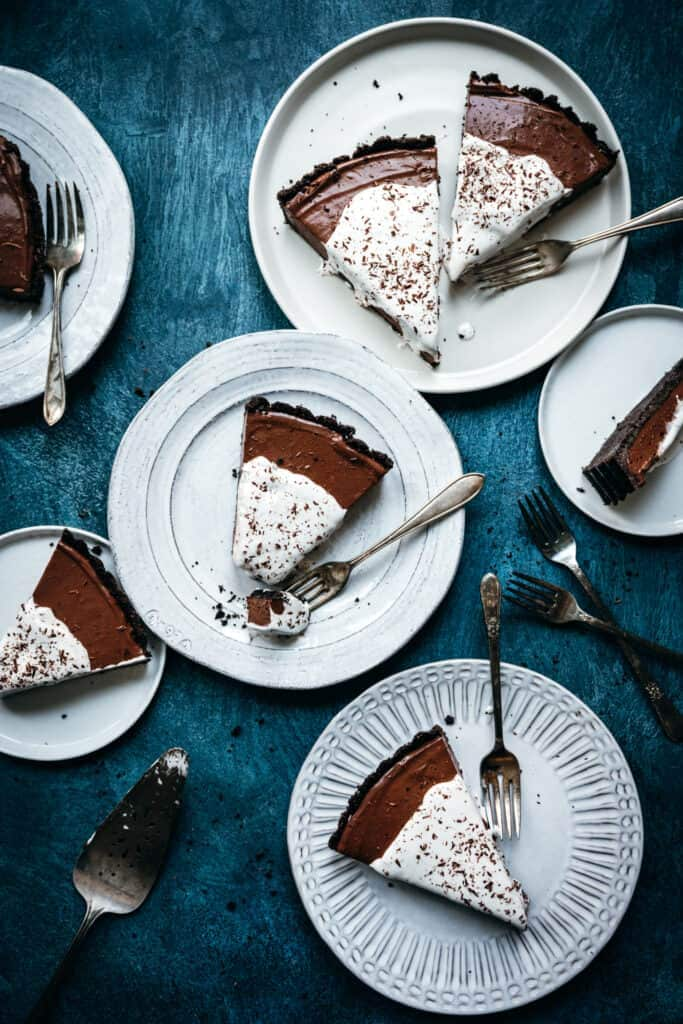 overhead view of multiple white plates with slices of chocolate cream pie