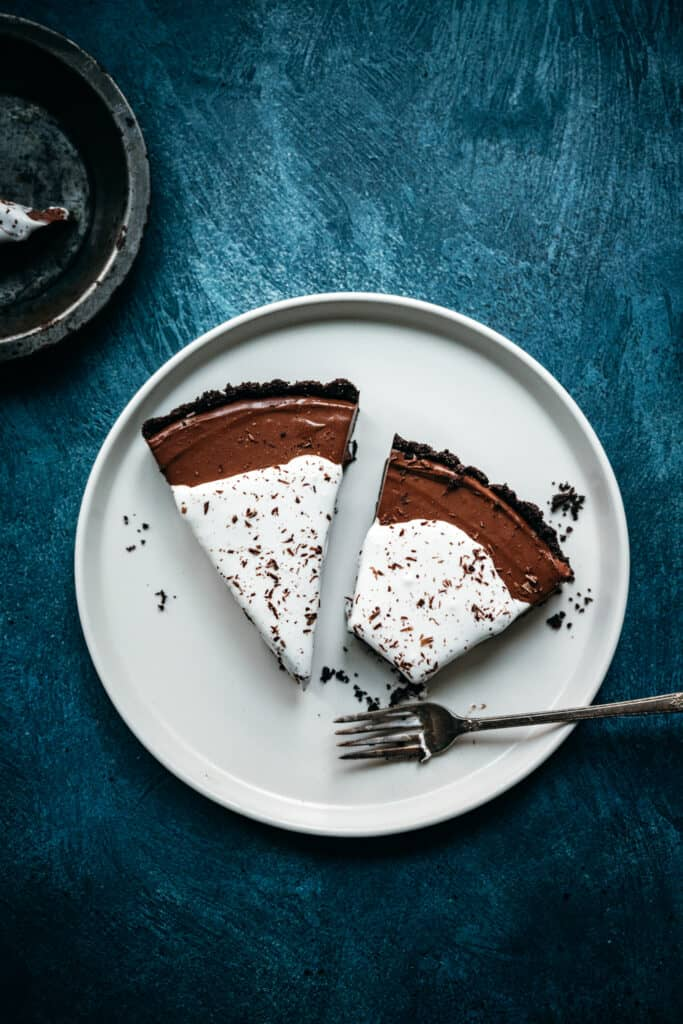 overhead view of large white plate with two slices of chocolate pie and a fork