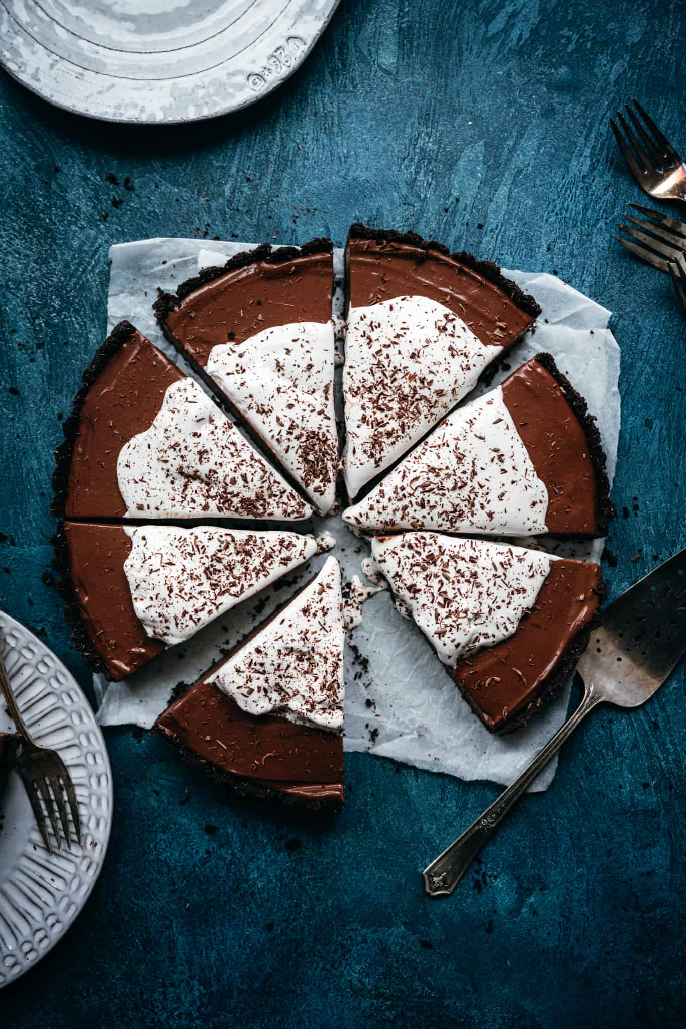 overhead view of vegan chocolate pie with whipped cream sliced into pieces