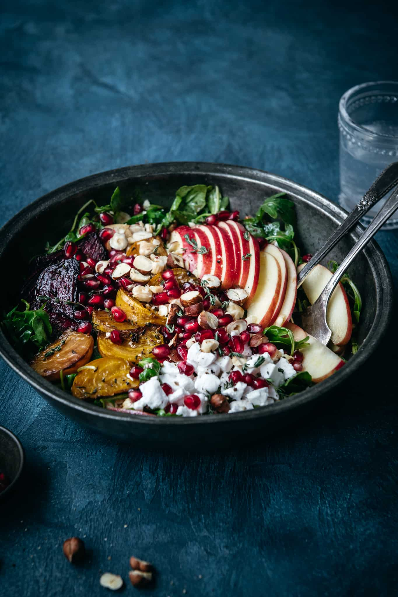 side view of roasted beet kale salad with hazelnuts, apple, pomegranate and feta in a large salad bowl