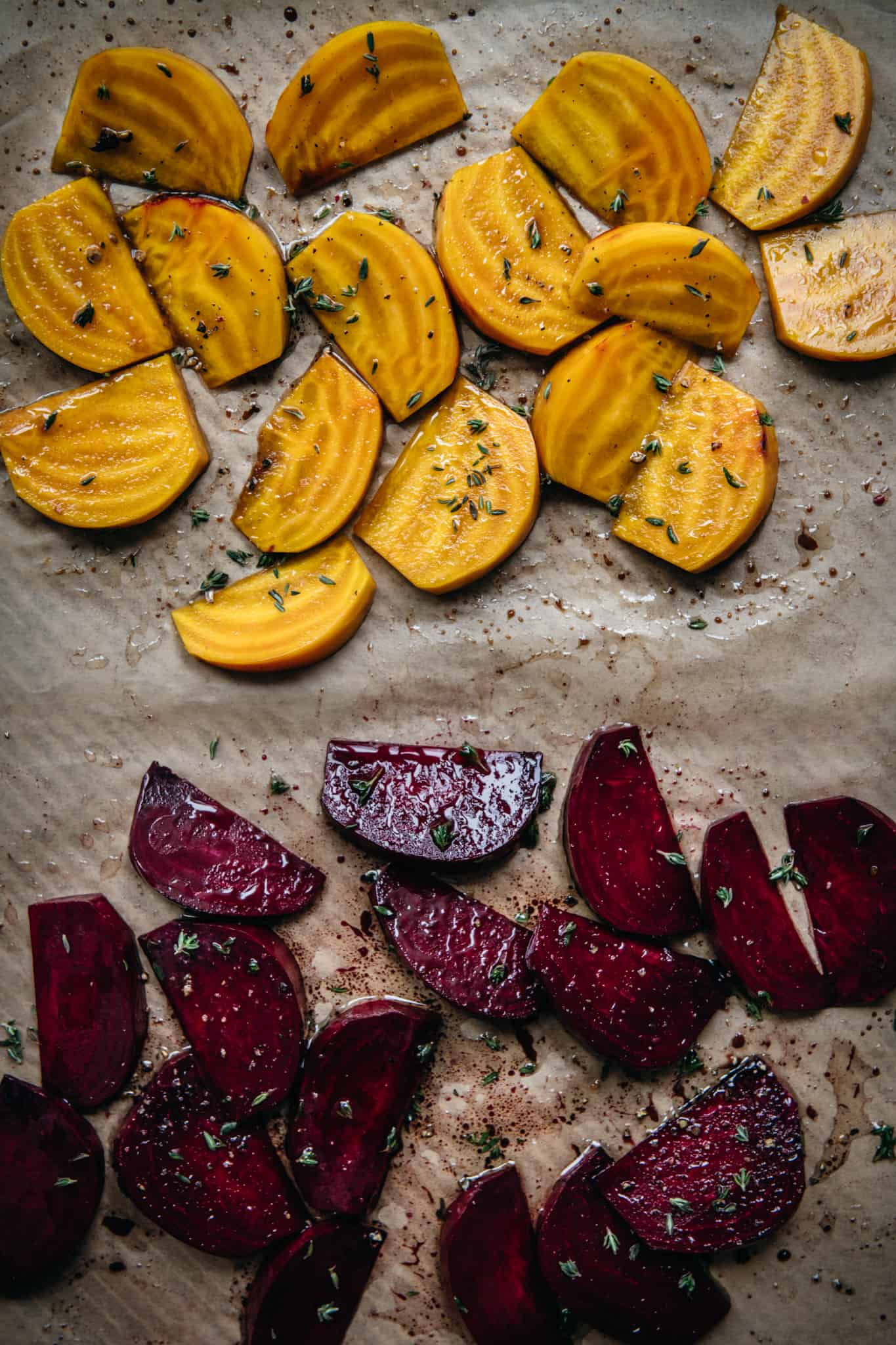 overhead view of golden and regular red beets on parchment paper