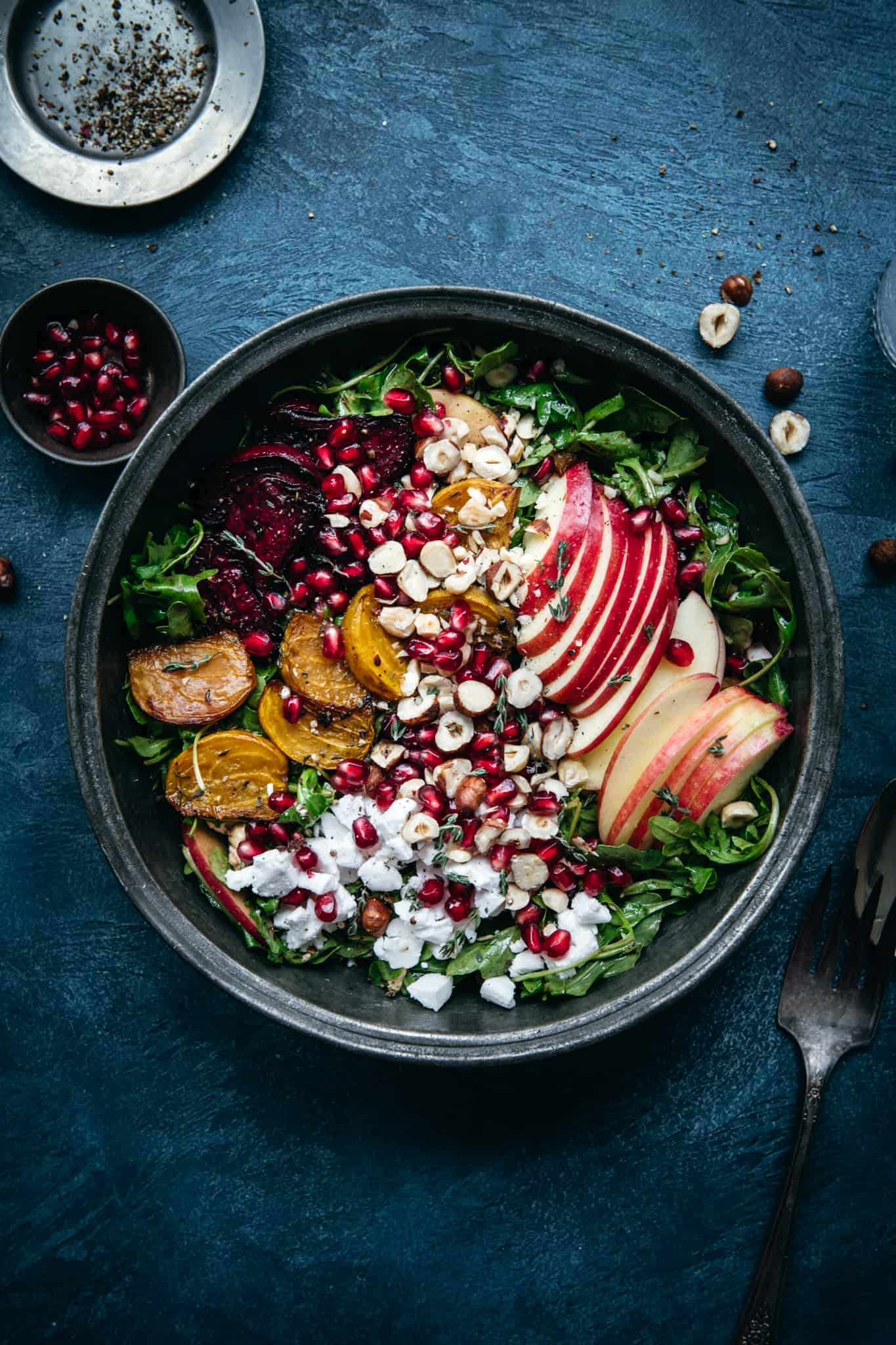 close up overhead view of roasted beet salad with vegan feta and kale