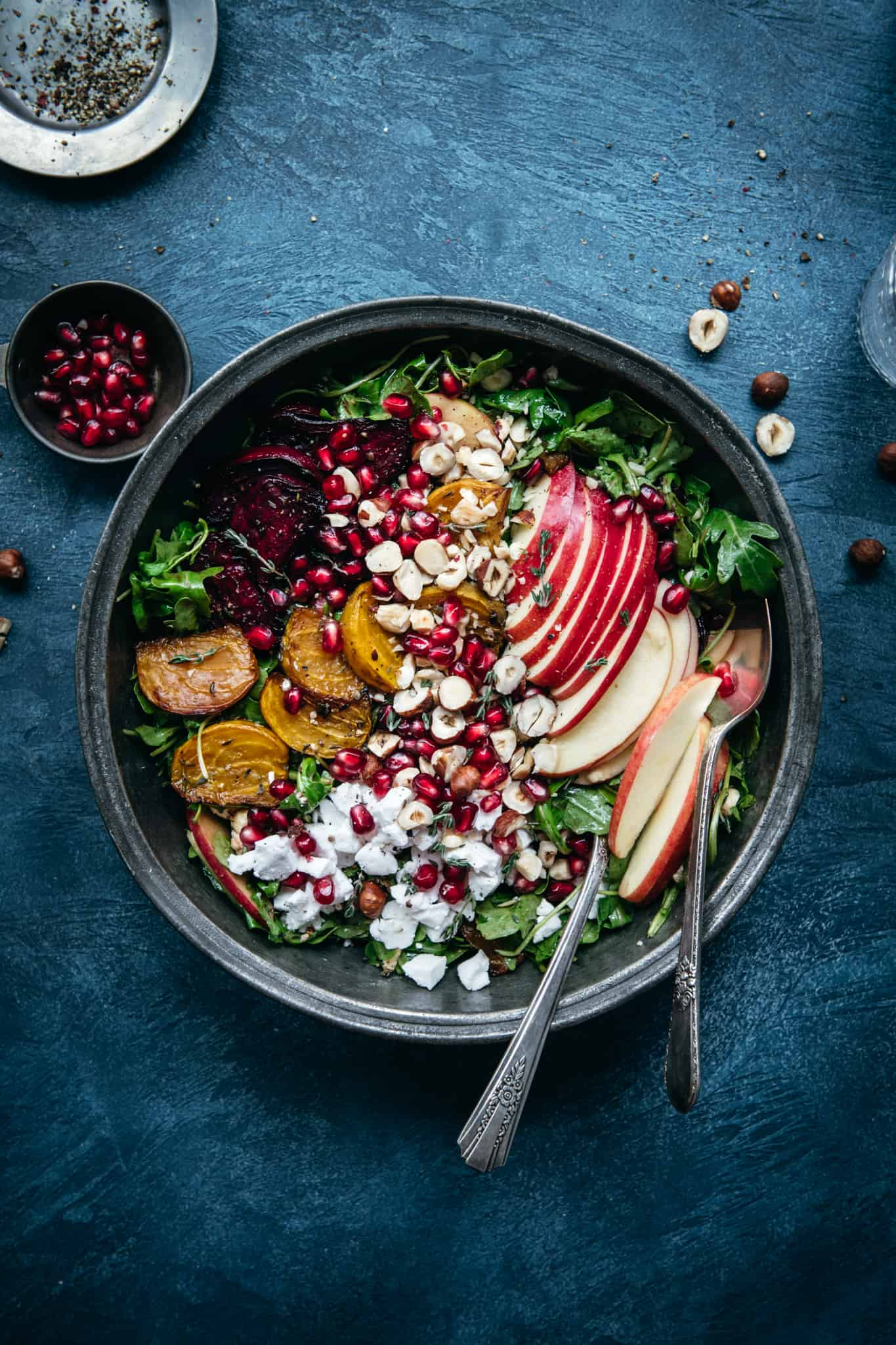 overhead view of beautiful roasted beet kale salad in a bowl on a blue background