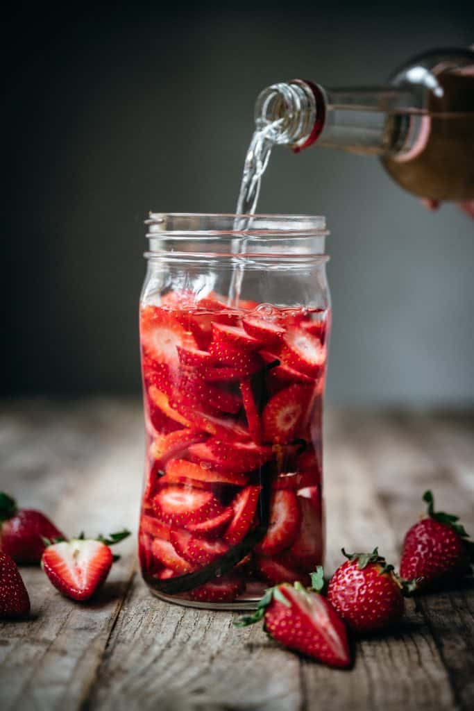 pouring vodka into jar with strawberries and vanilla