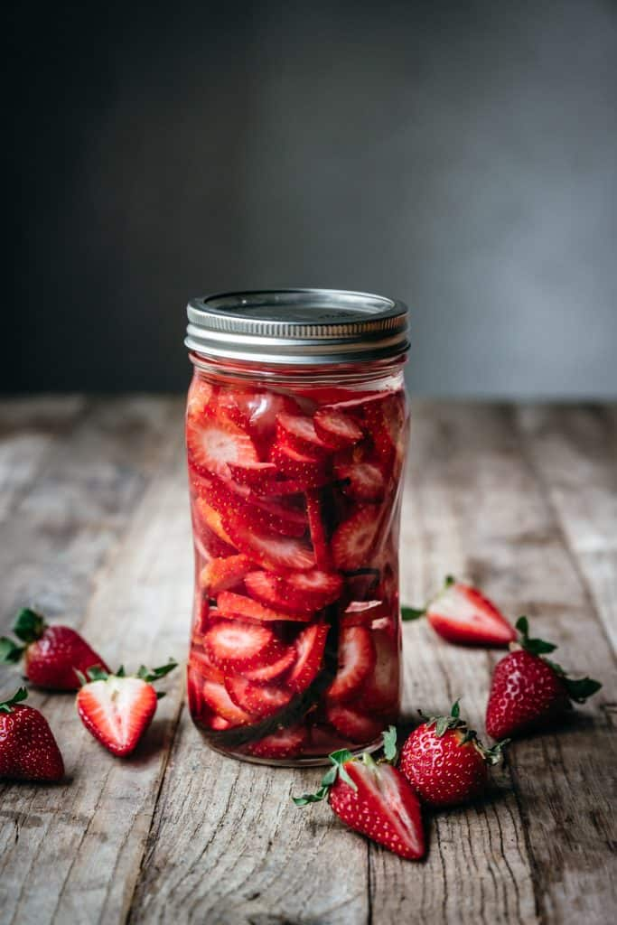 side view of strawberry vanilla infused vodka in a ball jar