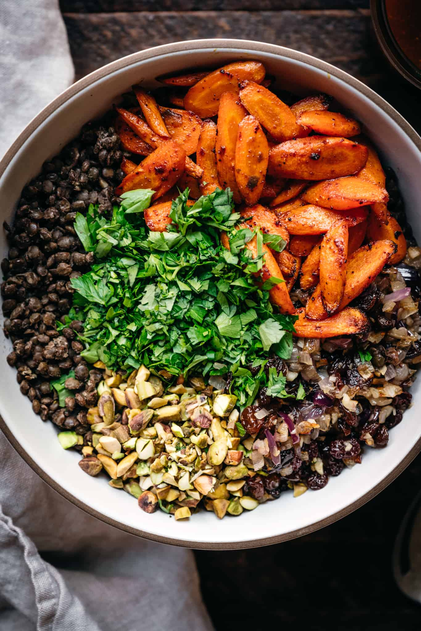 overhead view of ingredients in white bowl to make vegan french lentil salad with moroccan dressing