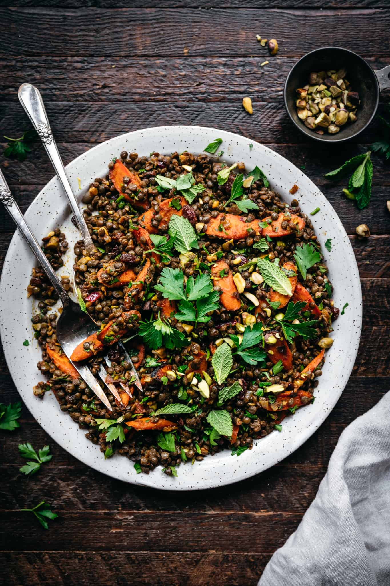 overhead view of moroccan lentil salad on a white plate with roasted carrots