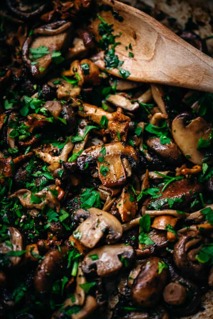 clsoe up overhead of panseared wild mushrooms in a skillet with a wooden spoon