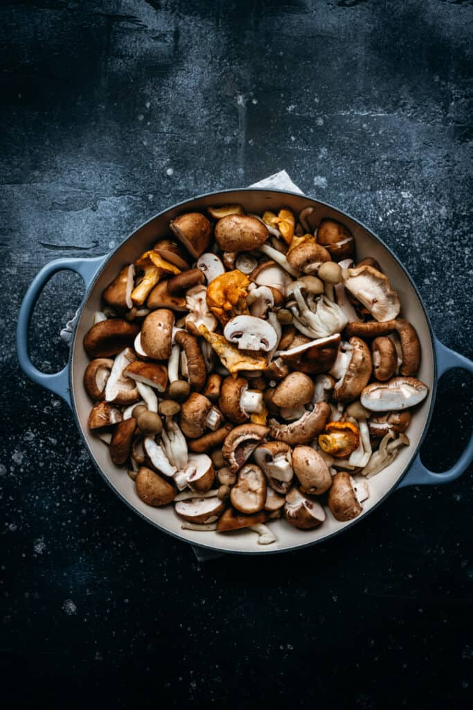 overhead of mixed wild mushrooms in a dutch oven
