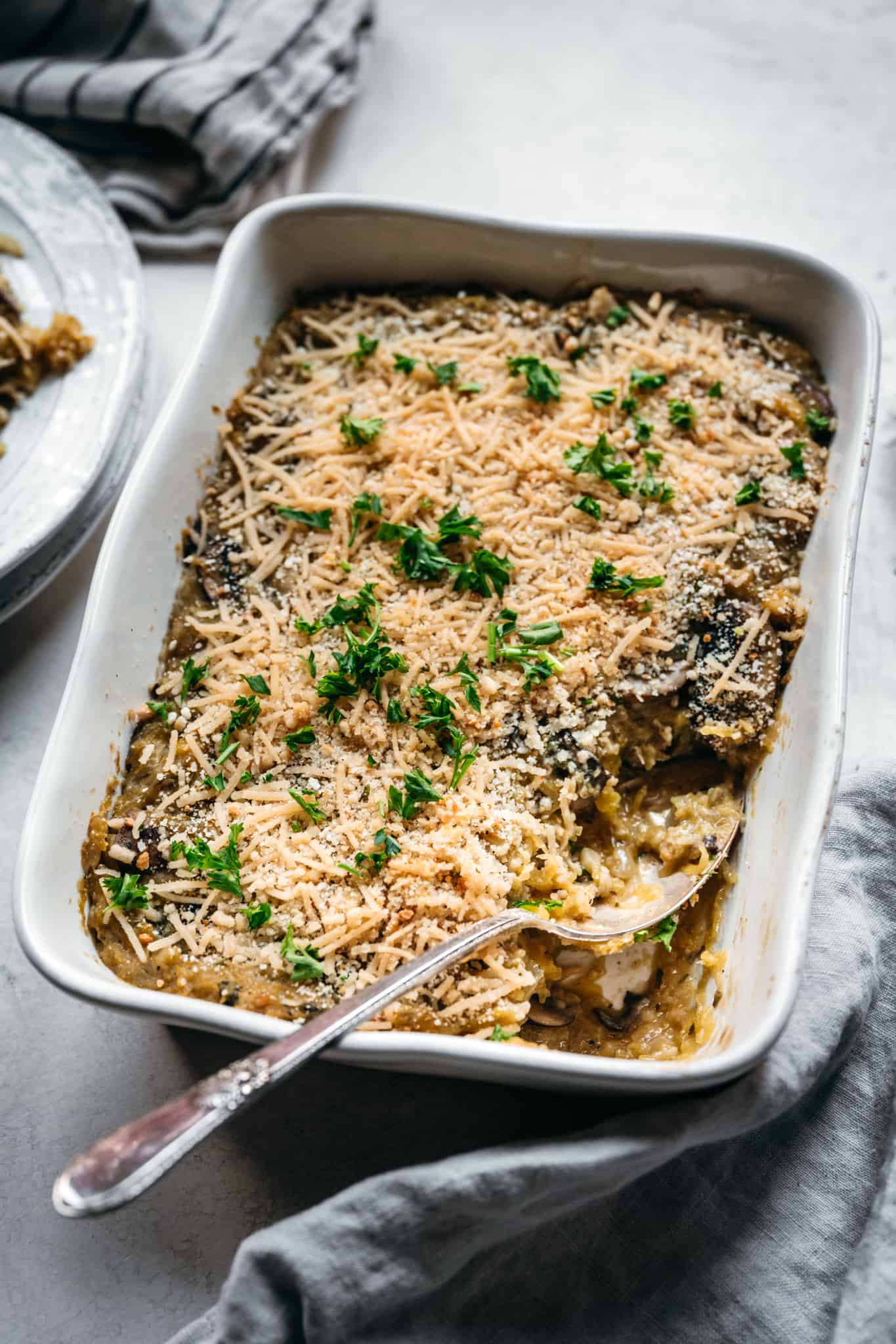 side view of vegan spaghetti squash casserole in white baking dish with spoon