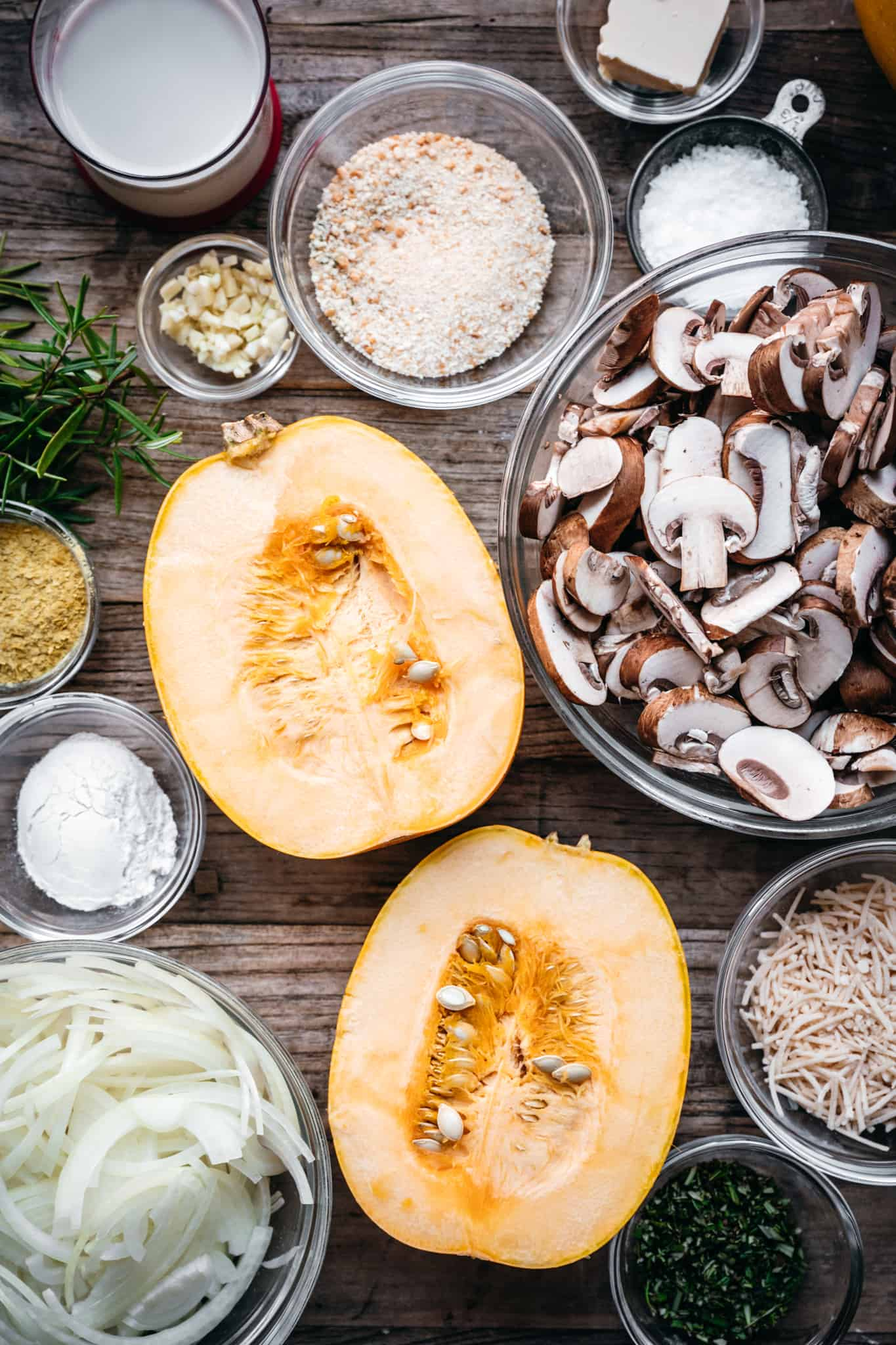 overhead of a spaghetti sqasuh, mixed mushrooms, and other ingredients for vegan casserole in small bowls on a wooden background