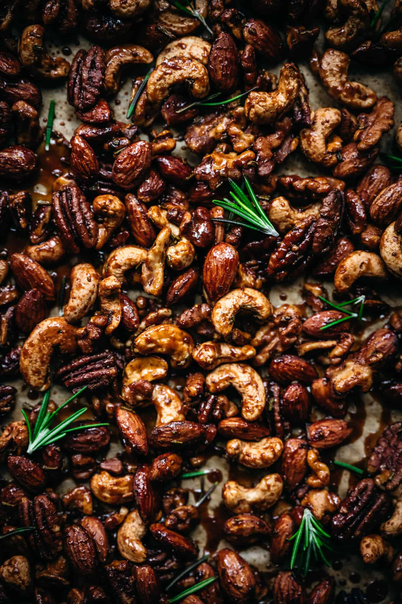close up overhead of vegan spiced nuts on a baking sheet with fresh rosemary sprigs