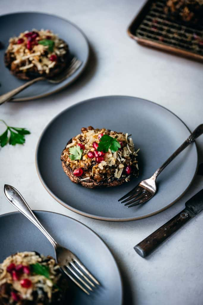 side view of stuffed portobello mushroom on blue plate with fork