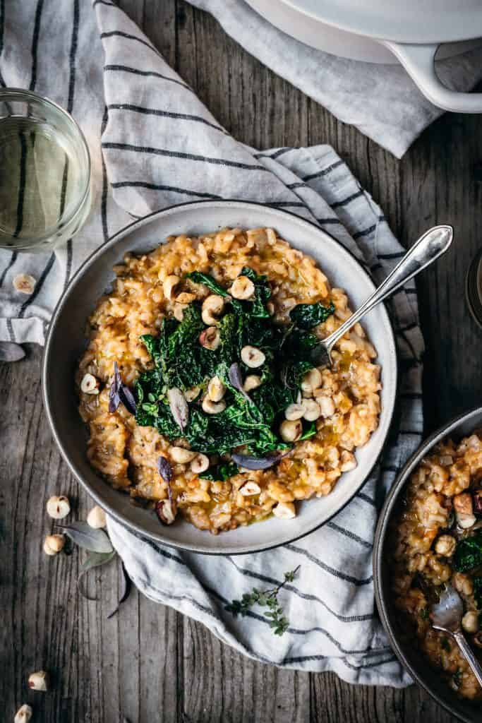 overhead view of sweet potato risotto with kale and hazelnuts in a ceramic bowl