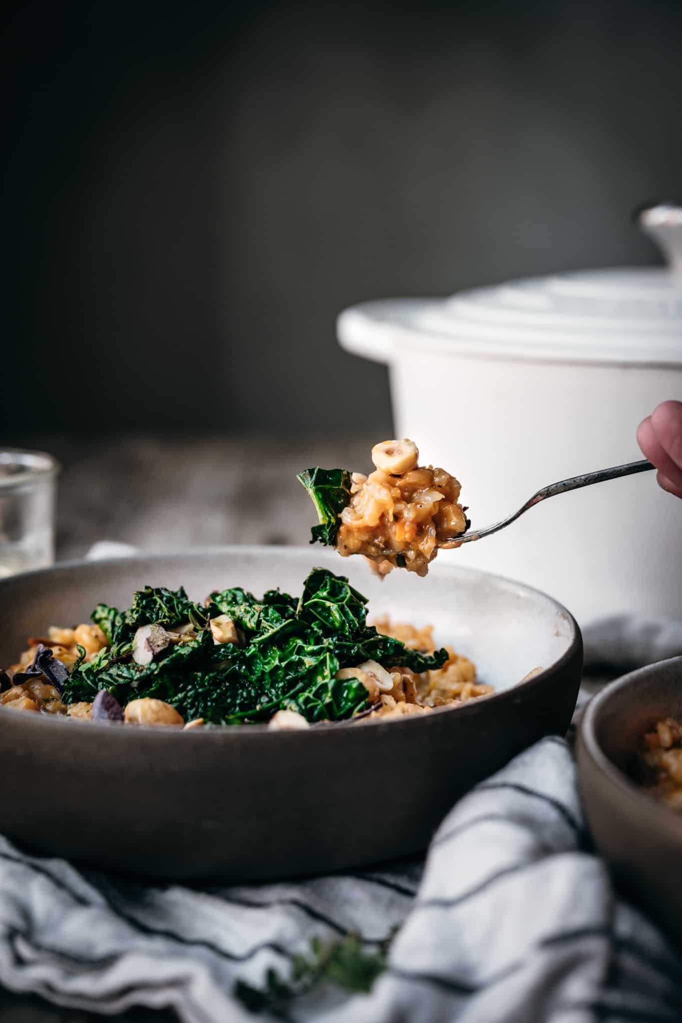 side view of forkful of vegan sweet potato risotto with kale and hazelnuts