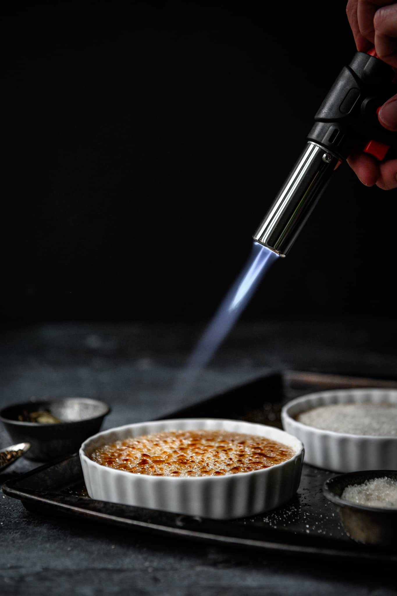 person using blowtorch to caramelize sugar for creme brulee