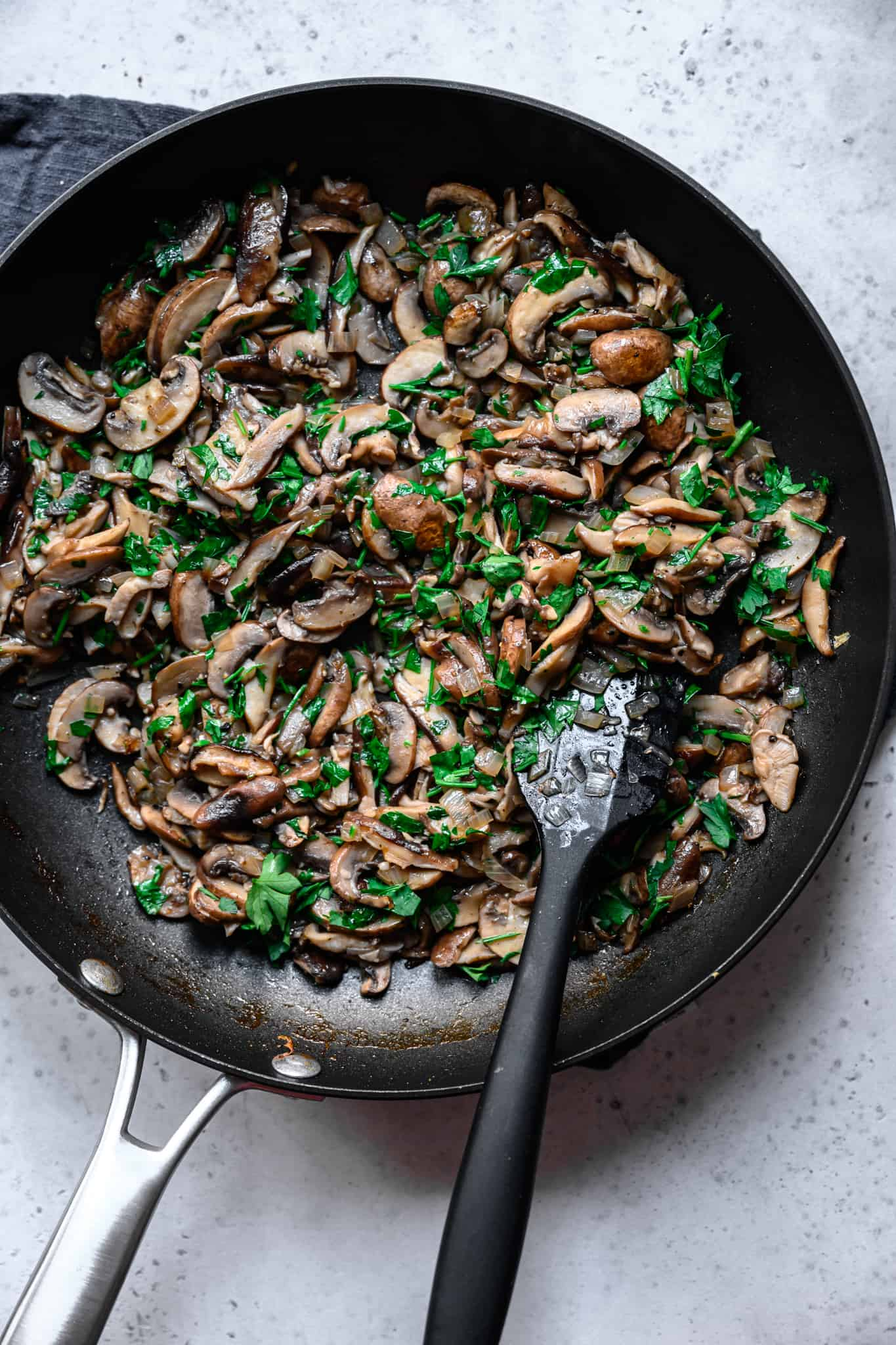 overhead view of cooked mushrooms in pan with parsley