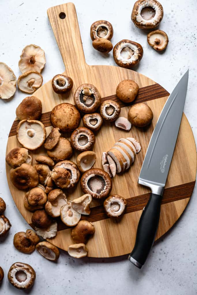 overhead view of button mushrooms on wood cutting board with knife