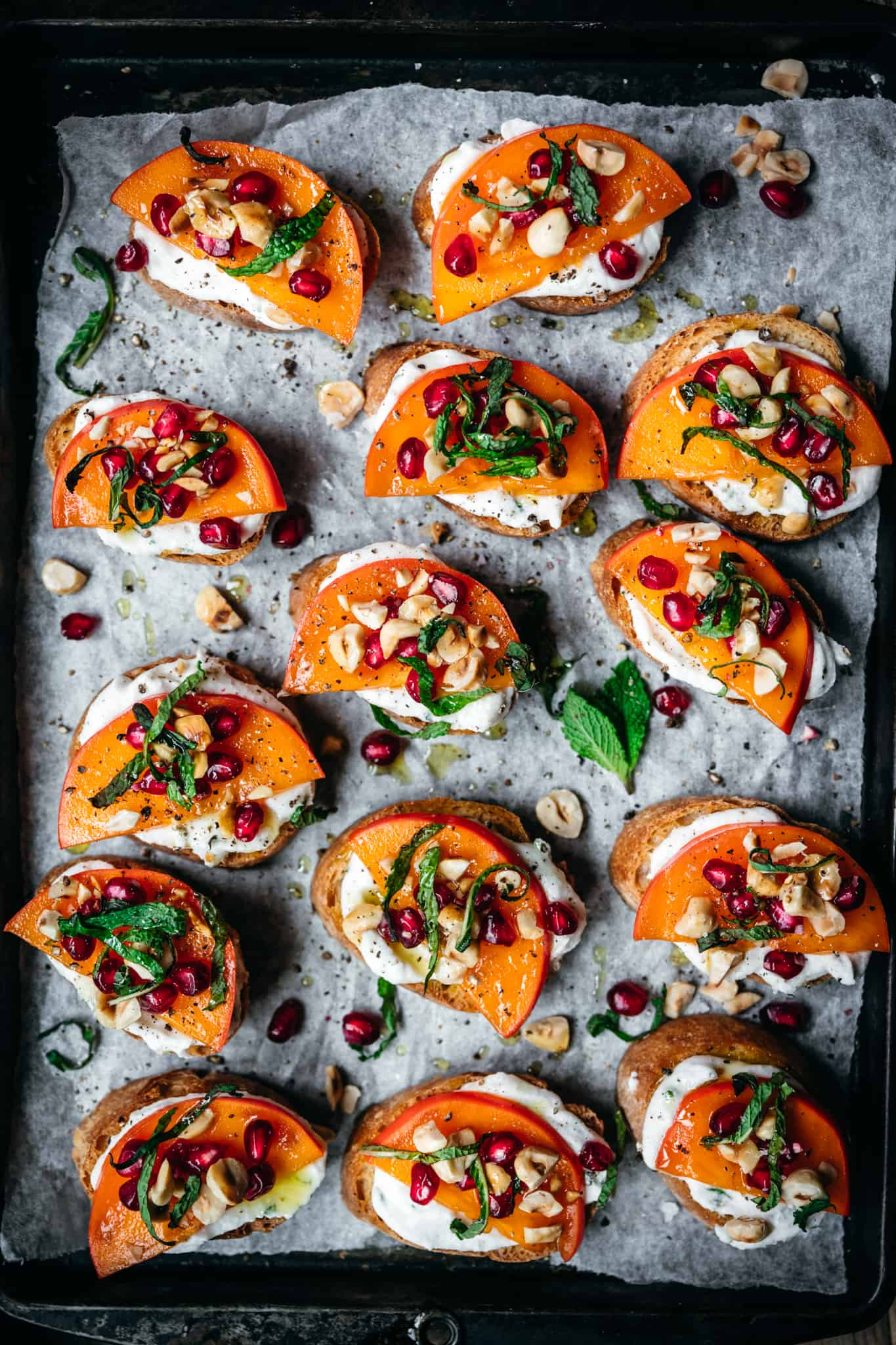overhead of vegan crostini with persimmon and pomegranate on a baking sheet