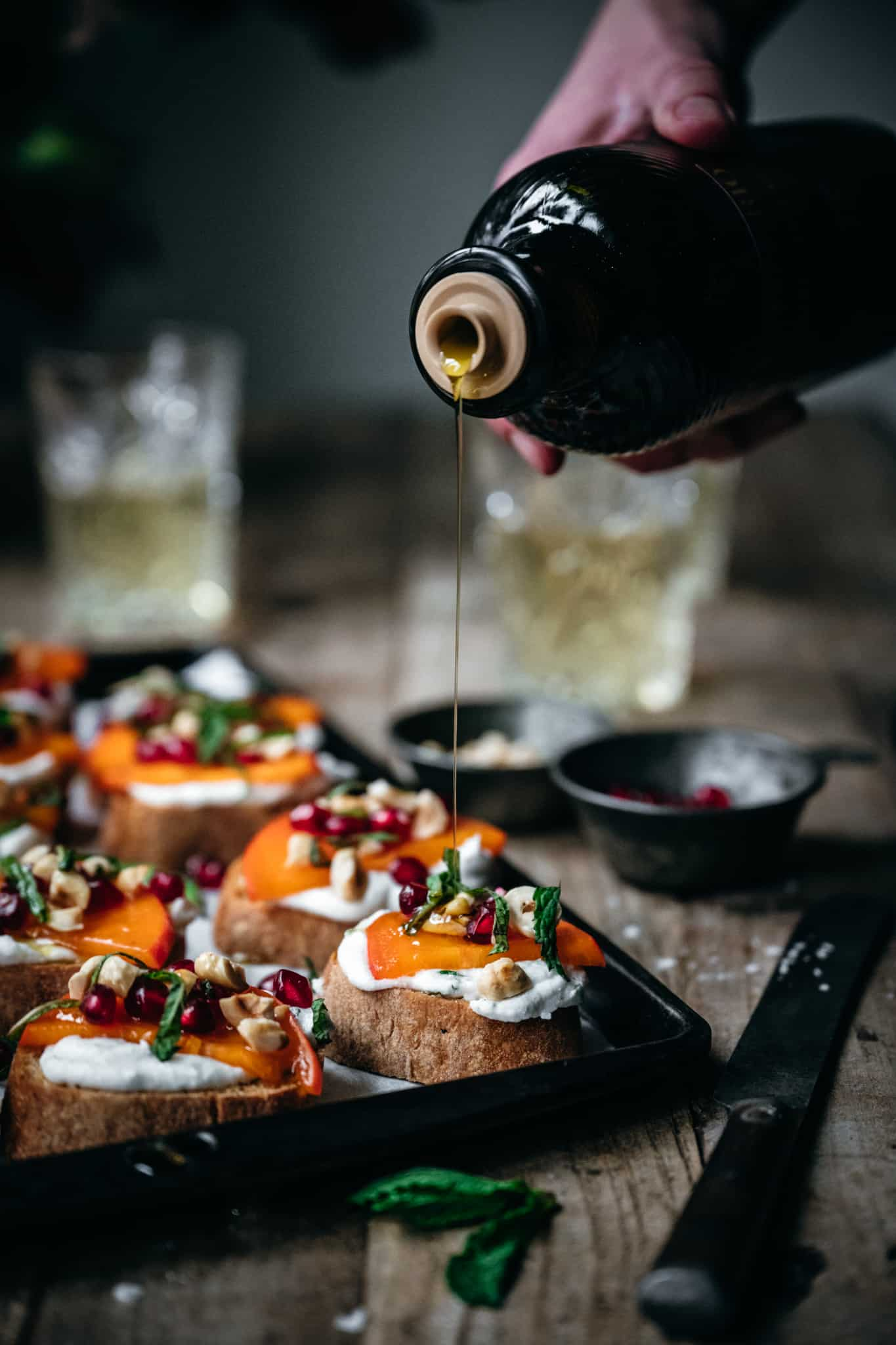 side view of a person drizzling the vegan crostini appetizers with olive oil