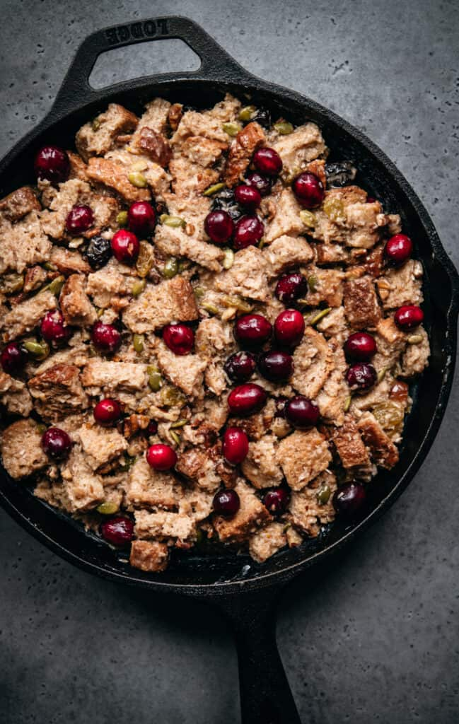 overhead view of unbaked cranberry bread pudding in cast iron skillet