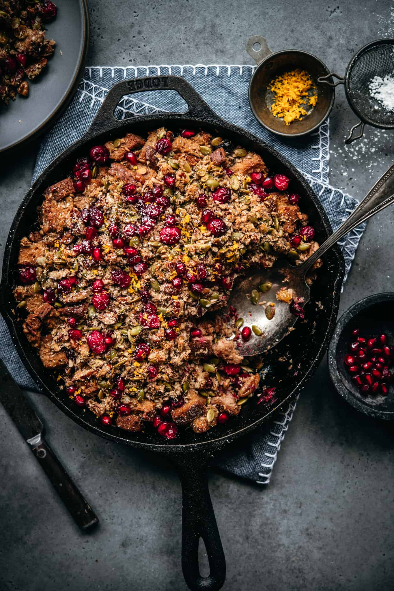 overhead view of gluten free cranberry cardamom bread pudding in skillet with serving spoon