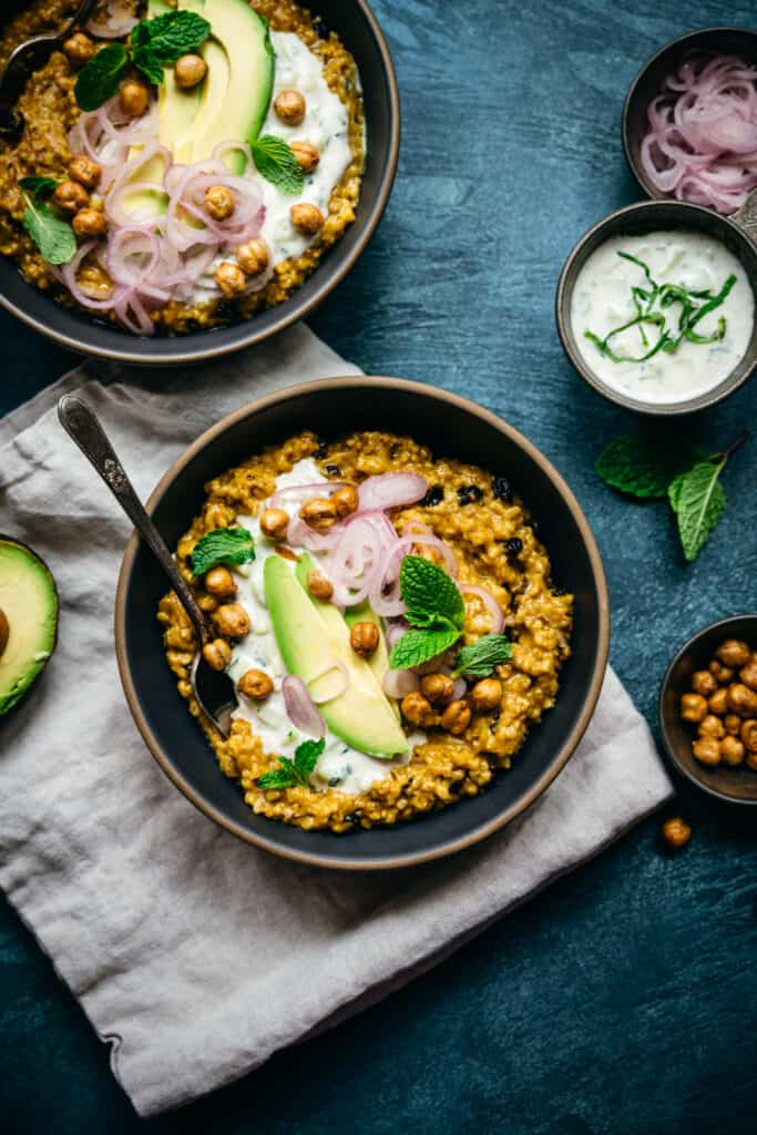 overhead view of savory indian-spiced steel cut oats with avocado, pickled shallots and chickpeas