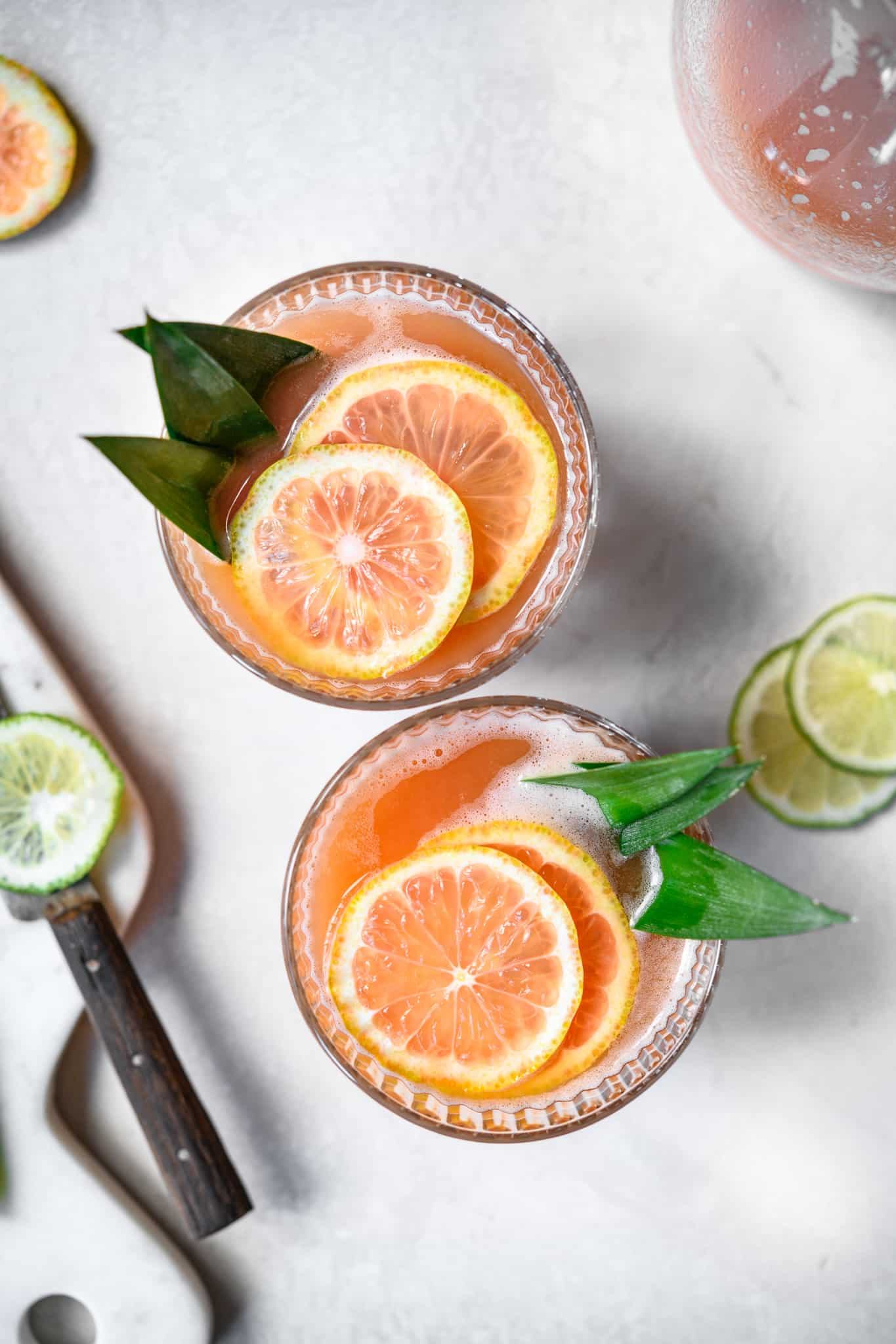overhead view of two guava cocktails with pink lemon garnish