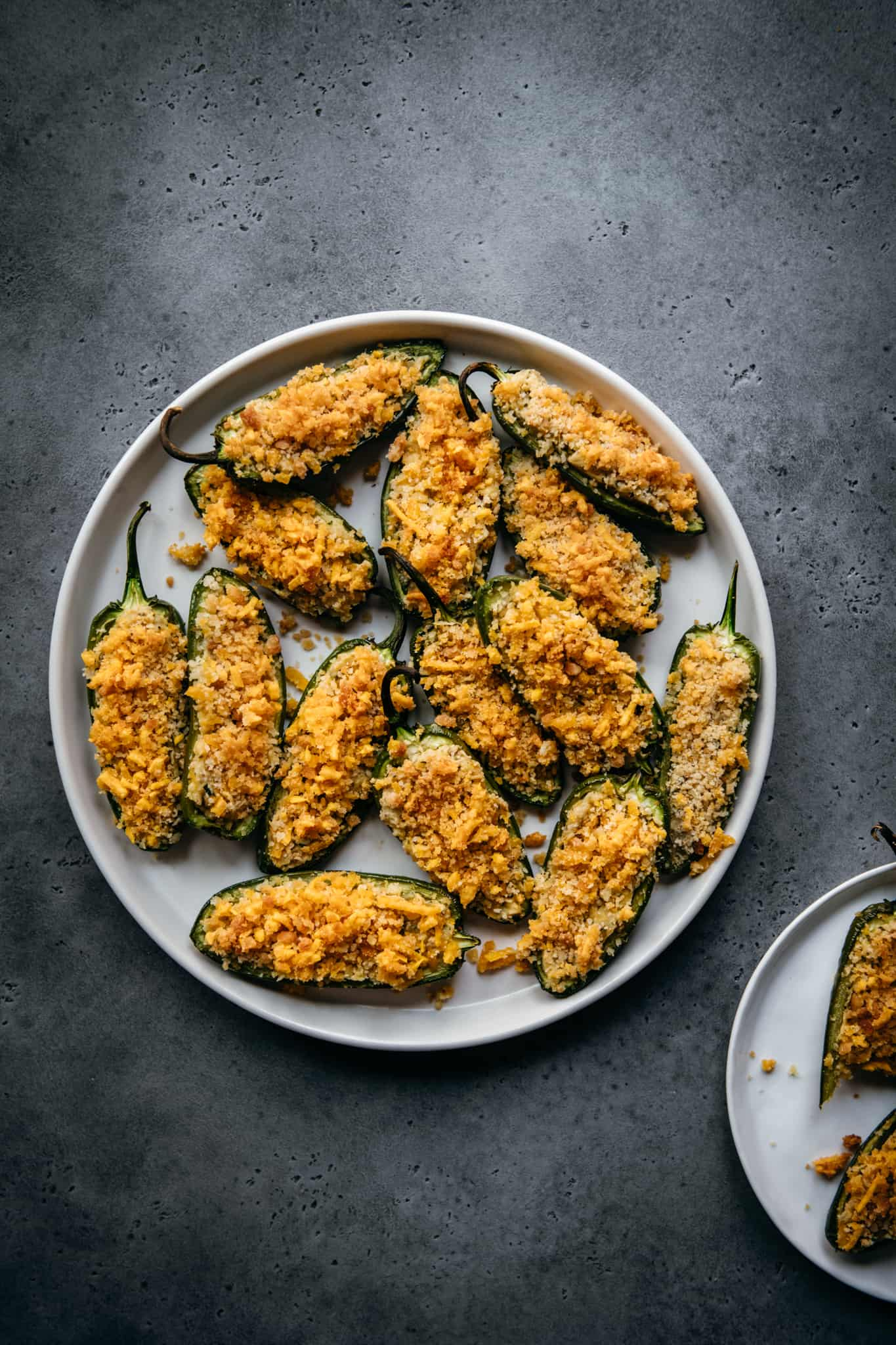 overhead of vegan jalapeno poppers on a white plate on a slate background