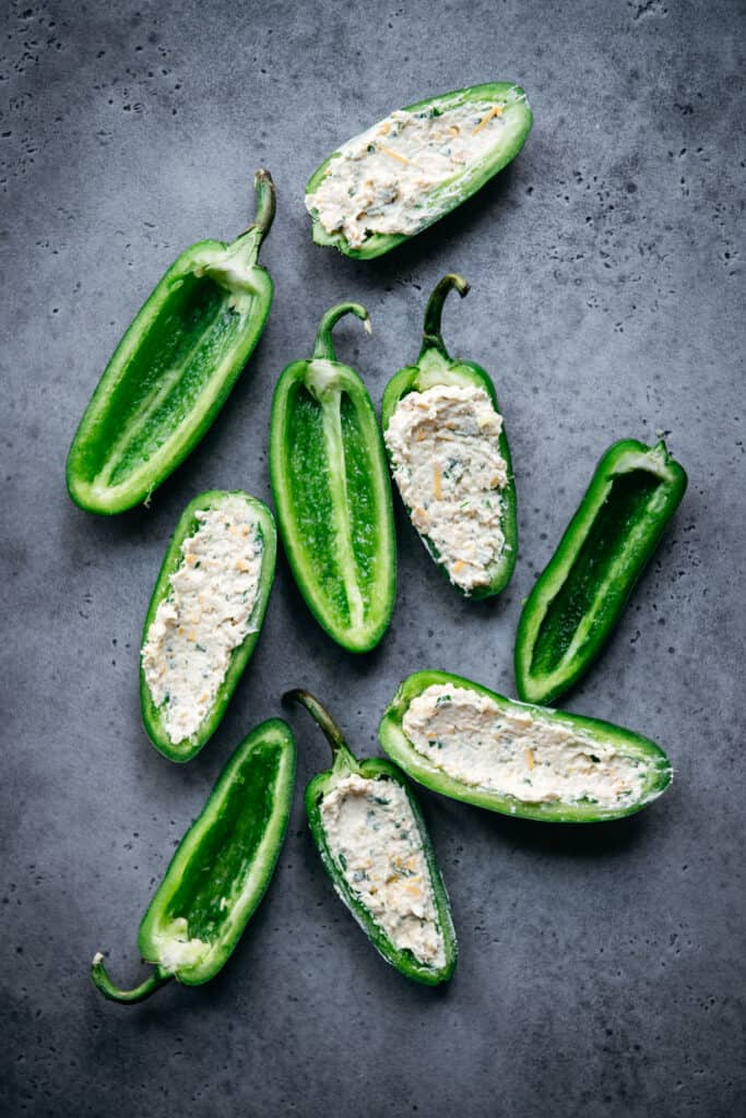 overhead of raw jalapenos, some with vegan cheese filling and some empty
