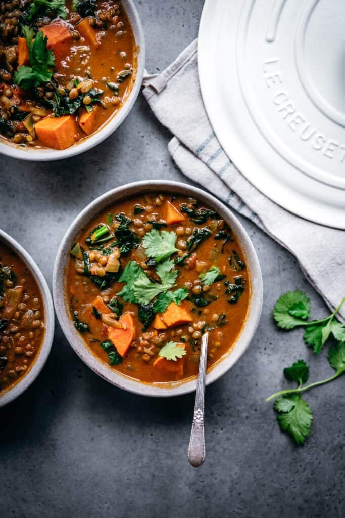 overhead view of lentil sweet potato curry soup in grey bowl with cilantro garnish
