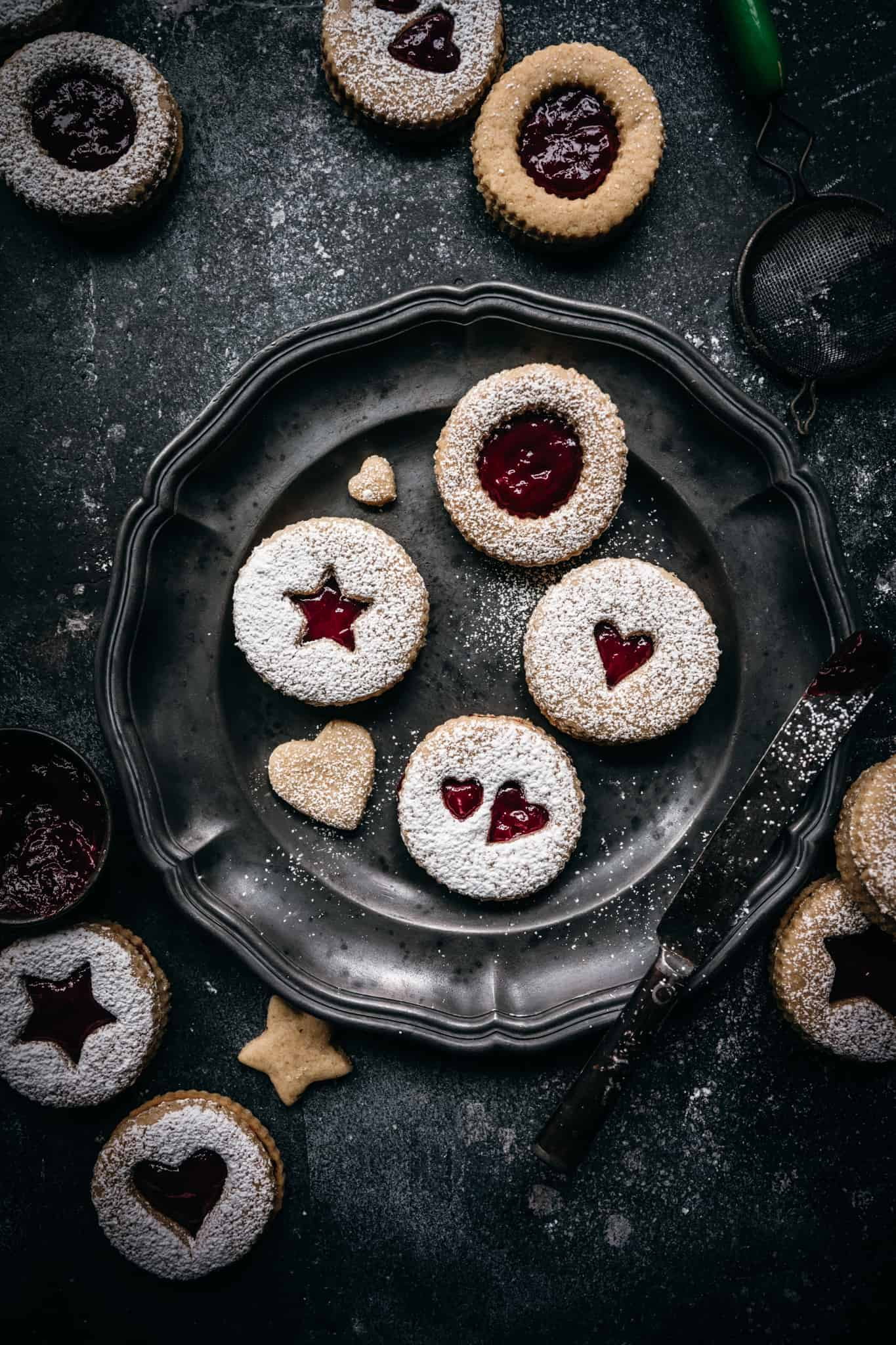 overhead view of raspberry linzer cookies on an antique plate