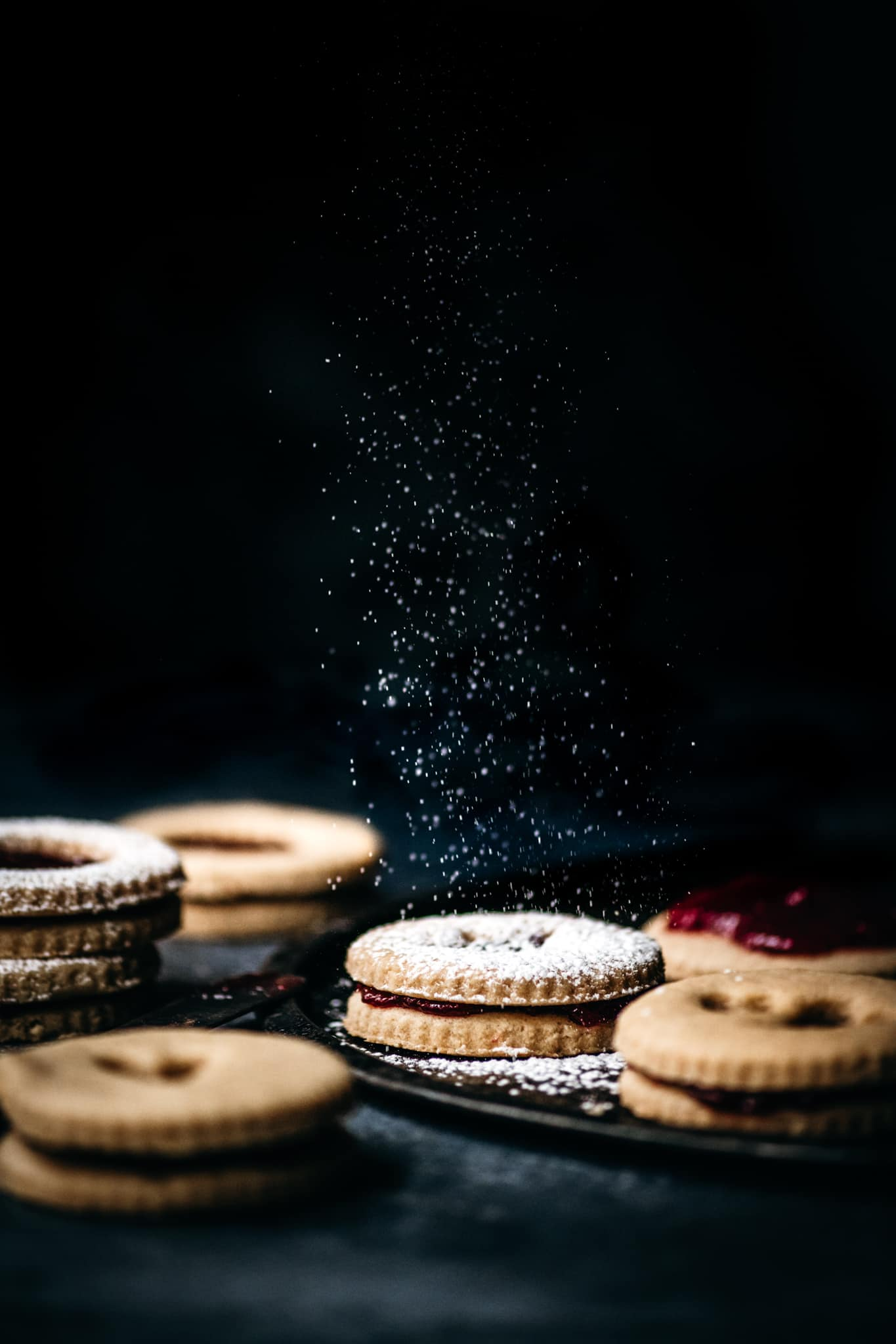 side view of dusting powdered sugar onto homemade linzer cookies