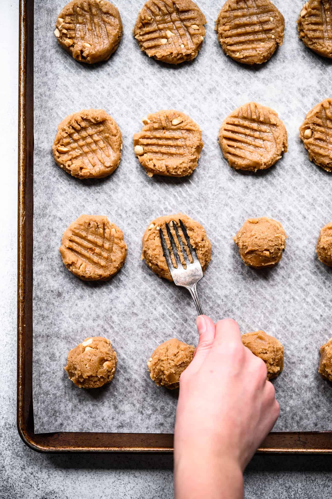 person using fork to flatten peanut butter cookie dough