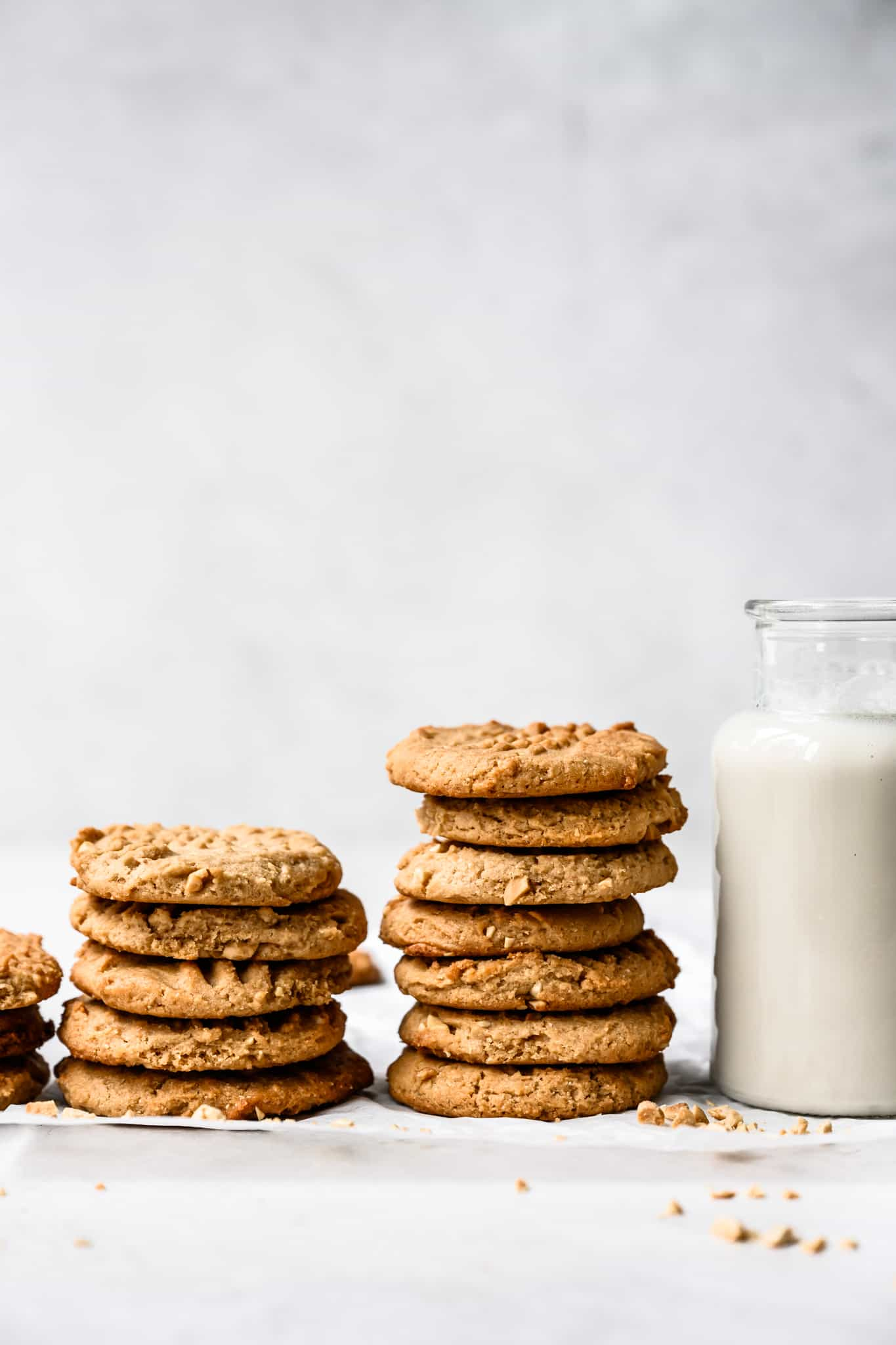 side view of two stacks of vegan gluten free peanut butter cookies next to glass of milk