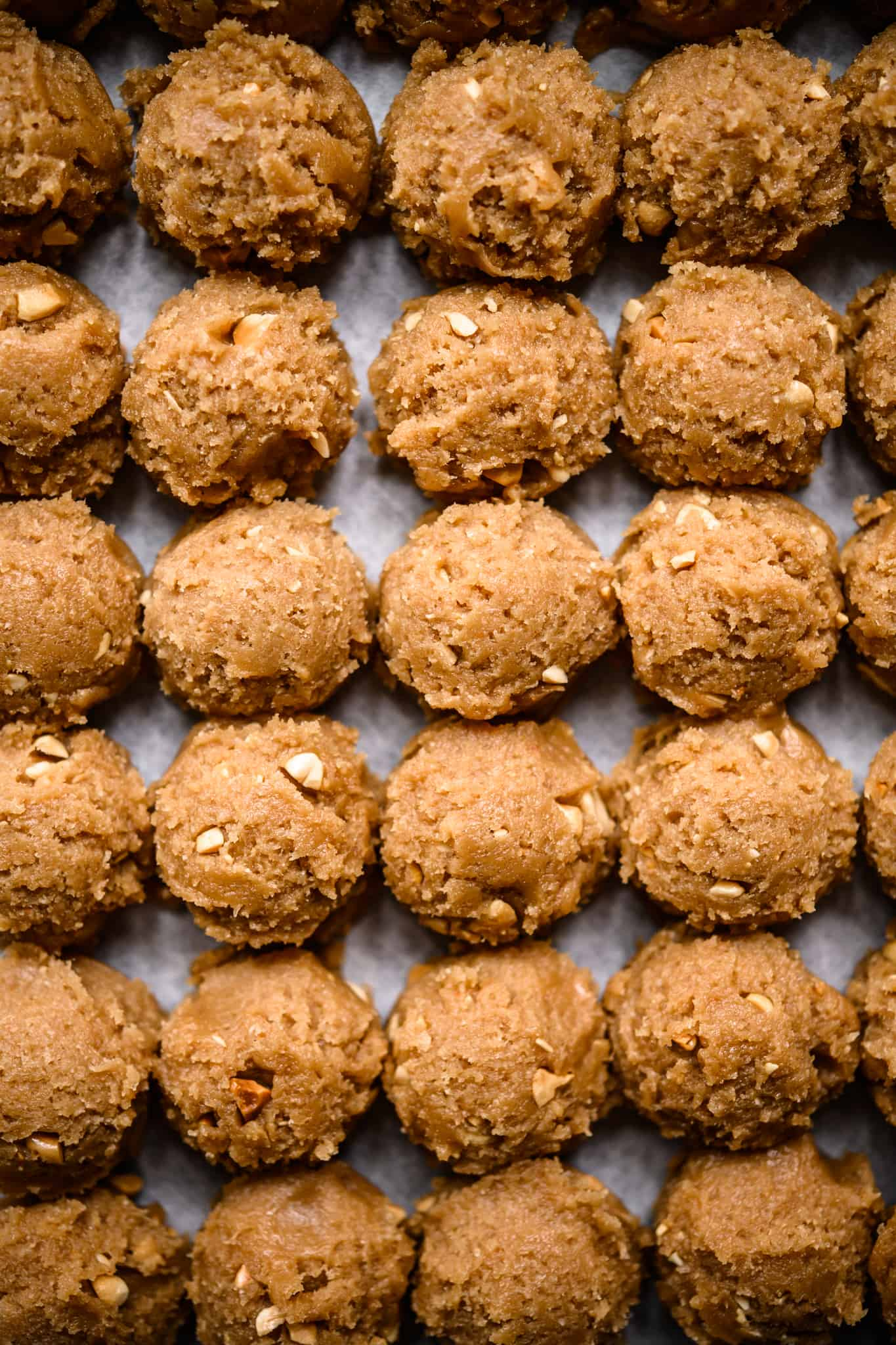 peanut butter cookie dough lined up on sheet pan before baking