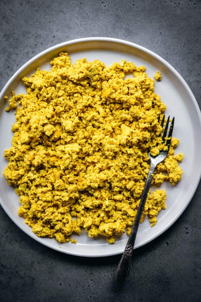 close up overhead view of vegan scrambled tofu on a white plate
