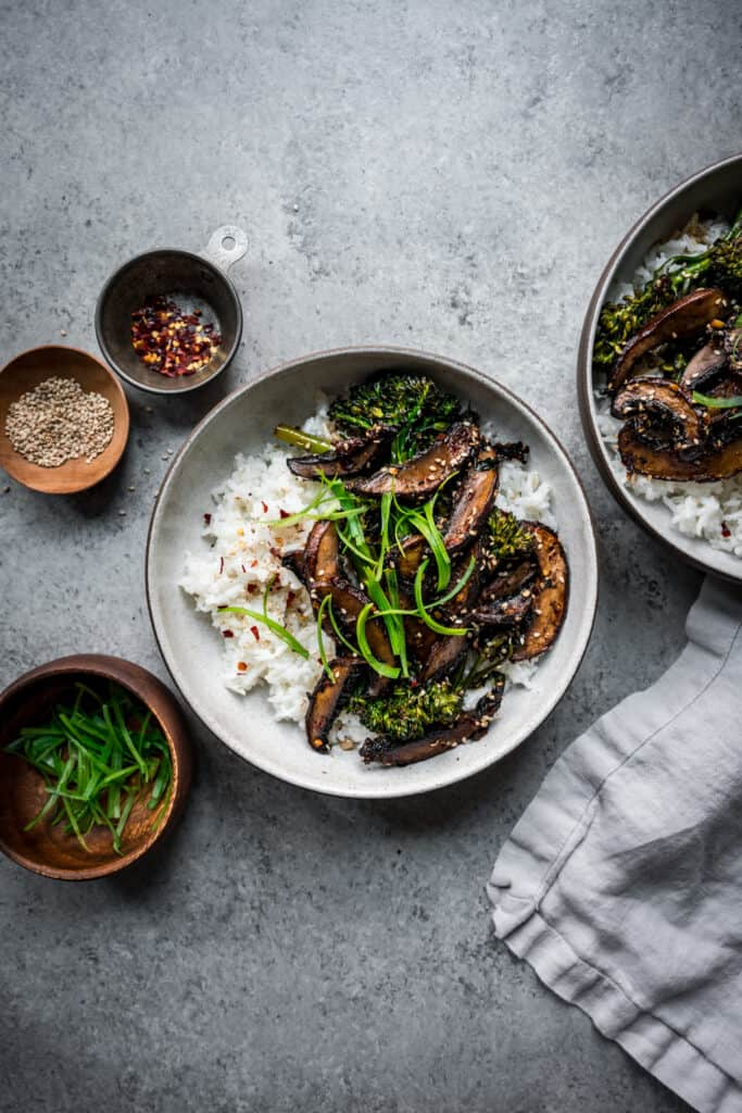 overhead of vegan teriyaki mushroom bowls on a light grey background
