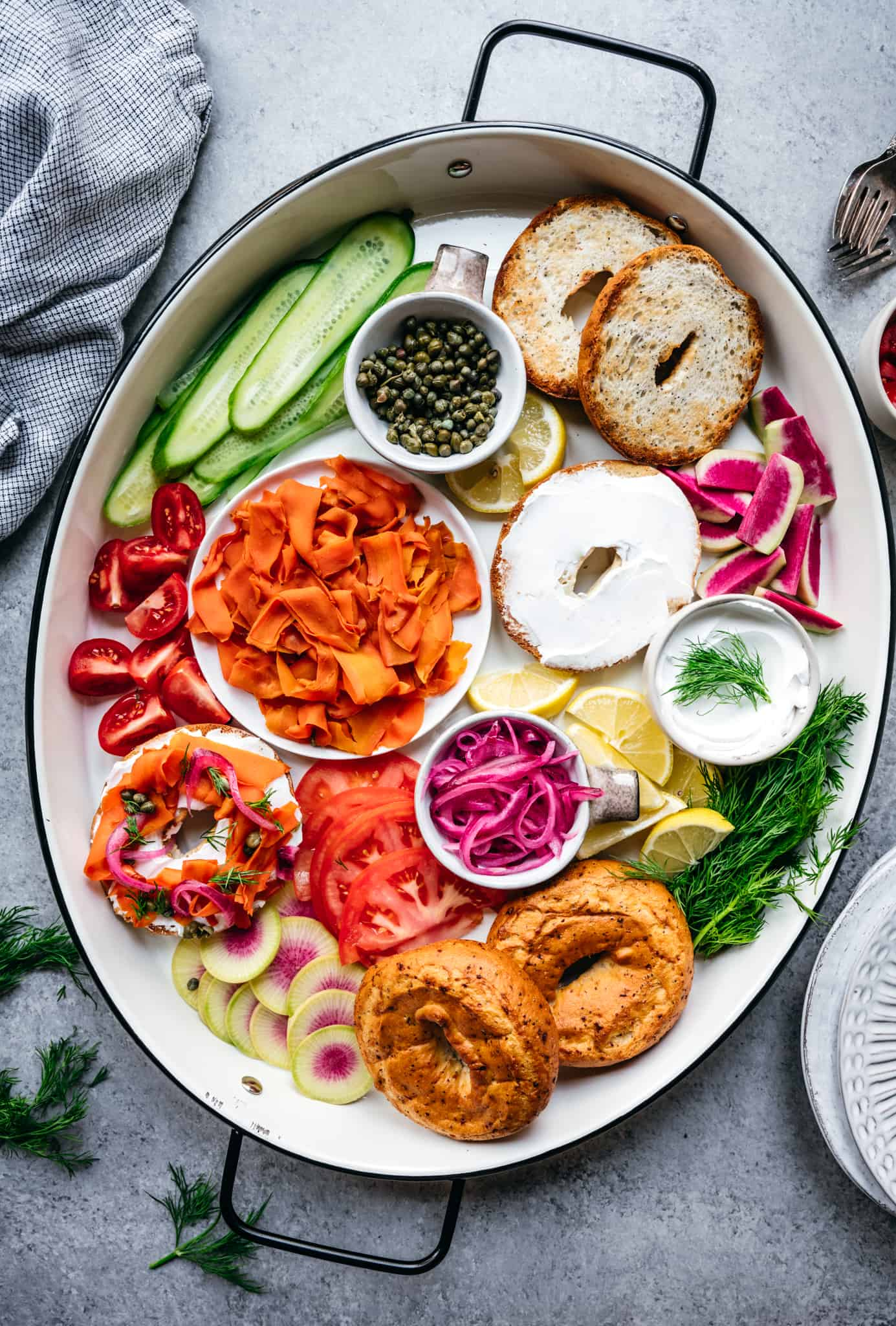 Overhead of a platter with homemade vegan carrot lox, bagels, cream cheese and other toppings for brunch